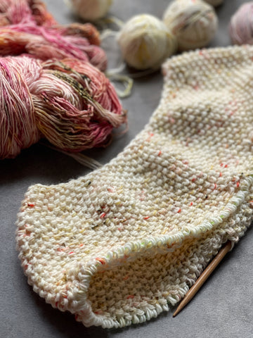 beginning of a top down knitted sweater surrounded by yarn