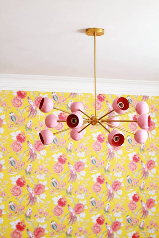 Pink Orion chandelier on yellow and pink floral wallpaper