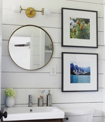 Mixing brass and black in a bathroom remodel with shiplap walls and a circular mirror