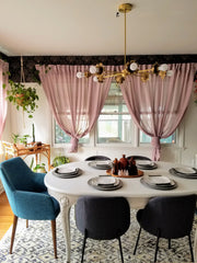 Floral dining room with wallpaper, white painted table, modern chairs, and a Victorian inspired chandelier