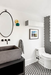 Black and white bathroom design with green and brass modern wall sconce