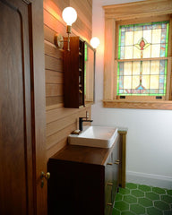 Rustic bathroom with green floral tile, stained glass window, and wood paneling