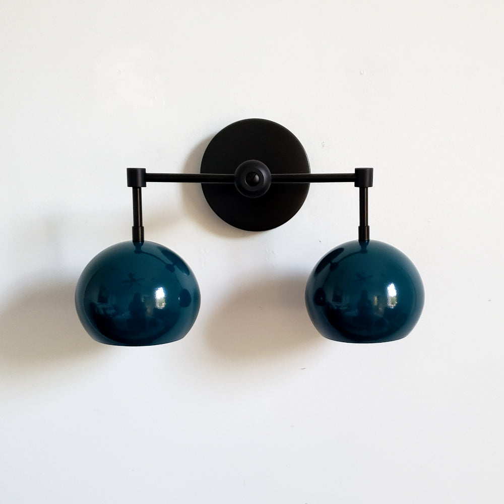 mid century modern inspired light with dark teal shades and matte black hardware.  The Double Loa sconce is a two light sconce that comes in fun colored shades and three metal options.