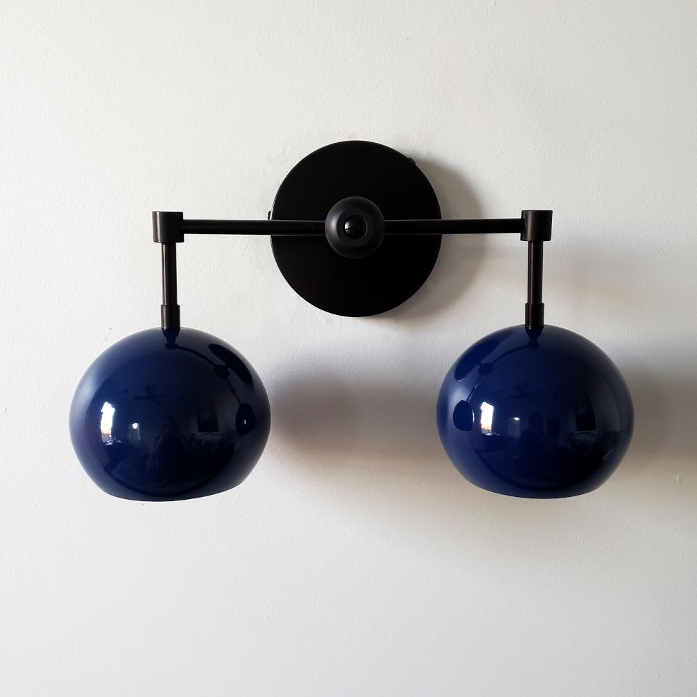 mid century modern inspired two light wall light with globe shades in navy and matte black.  Great for modern bathroom renovations, kids bathrooms, etc.