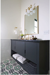 Grey bathroom vanity with brass accent and patterned tiled flooring