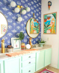 Tropical bathroom design with evil eye blue wallpaper and modern wall sconce
