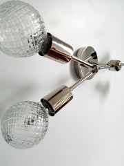 details of chrome wall sconce with crystal bulbs