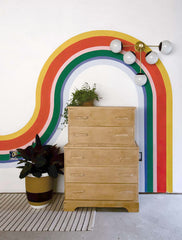 Rainbow mural, wood dresser, big rubber plant, and modern sconce by Sazerac Stitches