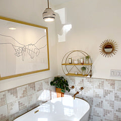 Boho style bathroom with southwest inspired tile, brass plumbing hardware, and modern art