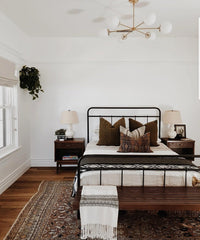 Brass modern chandelier in a neutral bedroom with brown decor