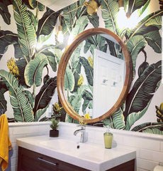 tropical themed bathroom wallpaper with a round mirror and a brass Magazine Sconce by Sazerac Stitches