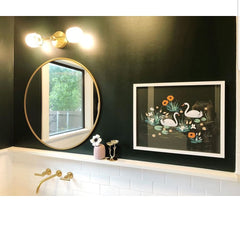 West End Sconce above a circular mirror on a dark green walls with wainscotting