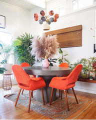 mid century modern dining room with Solaris Chandelier, concrete dining table, and orange dining chairs
