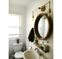 brass sconce over round mirror