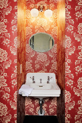 red floral bathroom with chrome wall sconce and white porcelain vanity sink