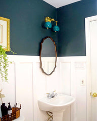 Green bathroom with a double loa wall sconce in green and brass