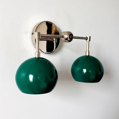 green and chrome two light wall sconce with mid century modern green globe shades