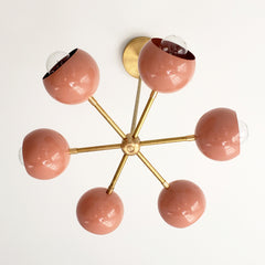 Peachy coral chandelier with brass accents and globe shades midcentury modern style updated