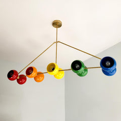 Large rainbow and brass chandelier with ROYGBIV colors.  Playroom kids room lighting