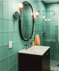 Orange and Chrome Camp sconces in a green subway tile bathroom