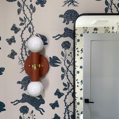terra cotta wall sconce on patterned navy and cream wallpaper