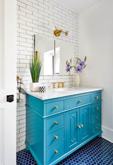 Colorful bathroom renovation with white subway tile, turquoise vanity, and cobalt blue flooring