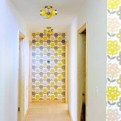 Yellow and brass mid century modern flushmount ceiling light in a retro style hallway