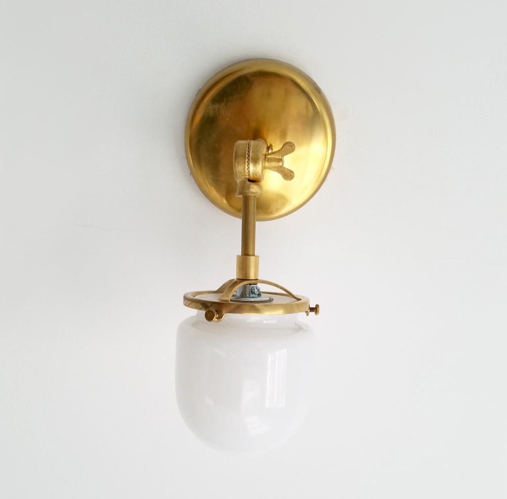 single articulating brass library sconce with glass