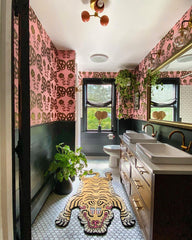 Boho Eclectic bathroom with wood vanity, tiger rug, and pink wallpaper