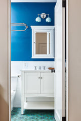 blue bathroom design with cobalt blue walls, mint flooring, and mint wall sconce.  Chrome accent metals