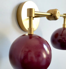 close up picture of brass black cherry double loa wall sconce