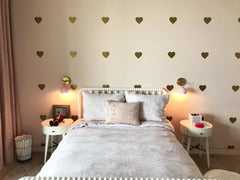 Pink Loa sconces with gold heart wallpaper