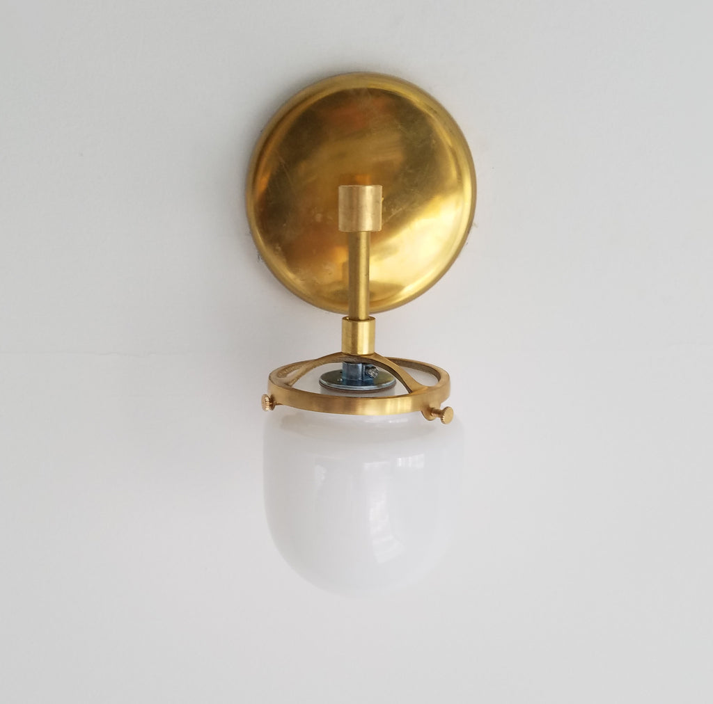 single brass bathroom sconce with glass