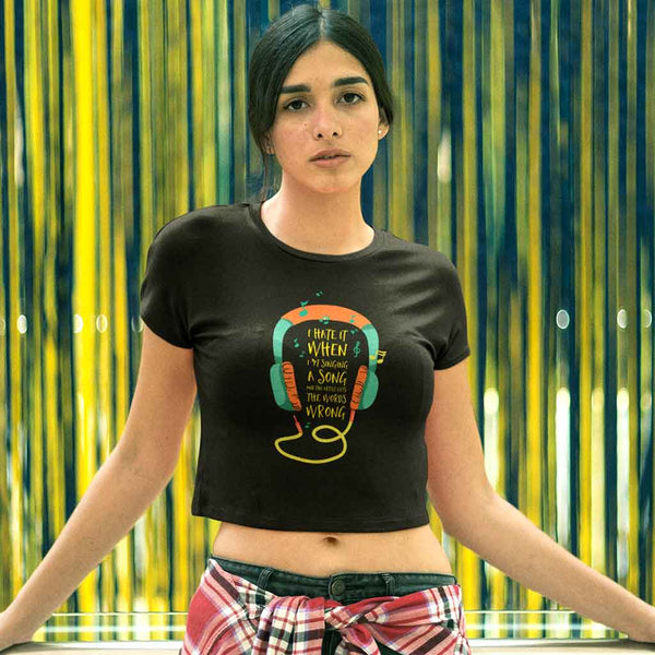 woman-wearing-crop-t-shirt-black-against-a-blue-and-yellow-background