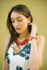 woman wearing coral colored necklace and bracelet handmade fair trade jewelry
