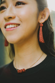 woman wearing burgundy tassel earrings looking ahead