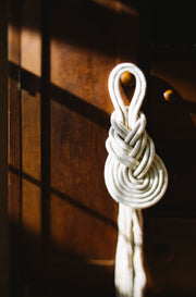 Knotted rope looped into a decorative wall hanging with long tassel