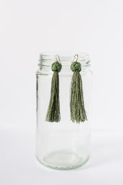 green knotted earrings handmade ethical earrings hanging on glass jar