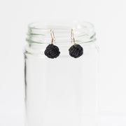 black drop earrings hanging on clear mason jar