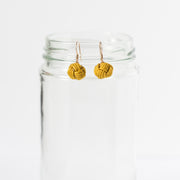 mustard yellow drop earrings hanging on glass jar