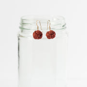 burgundy color drop earrings hanging on glass jar