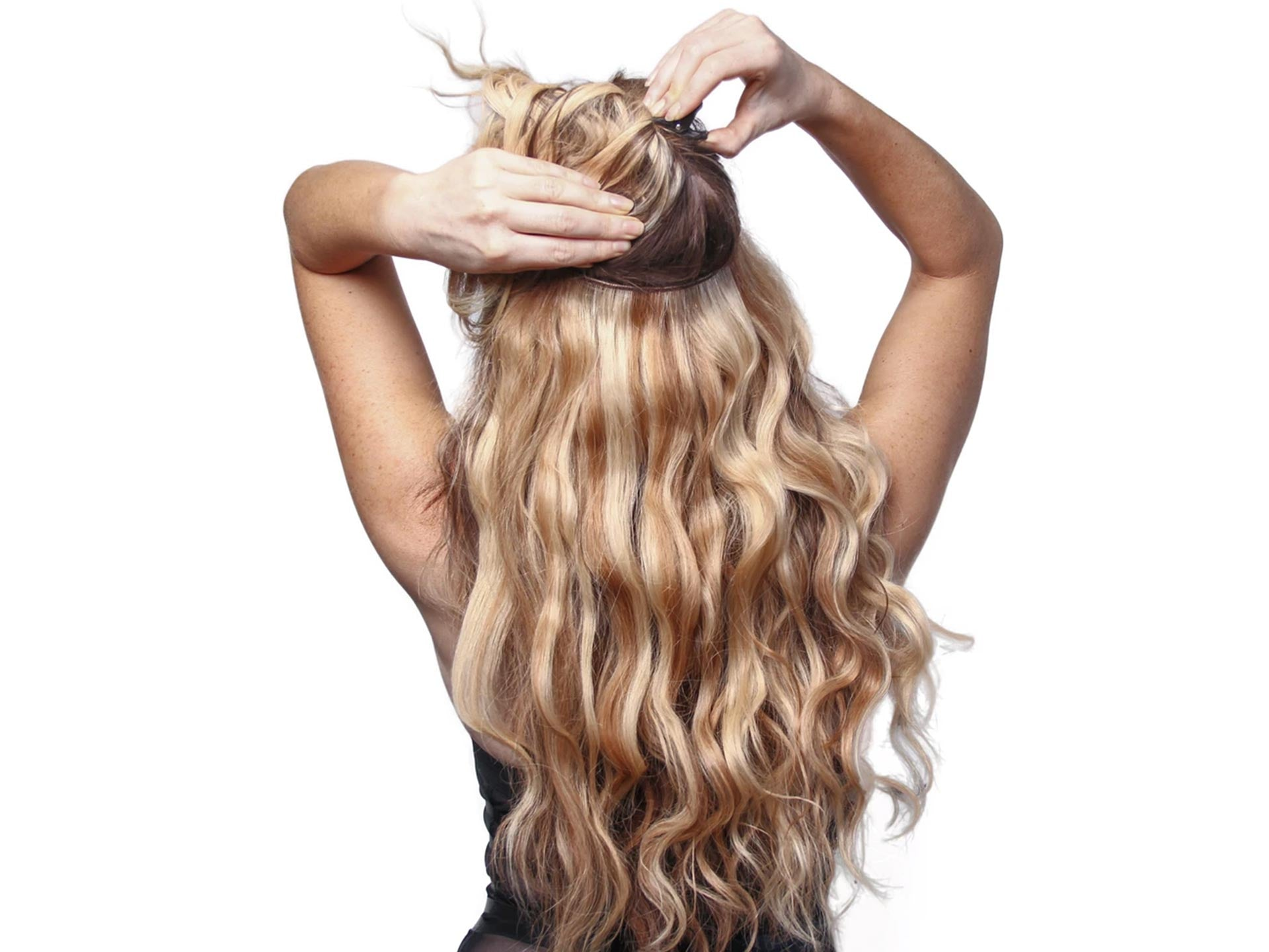 a lady is applying her halo hair extensions