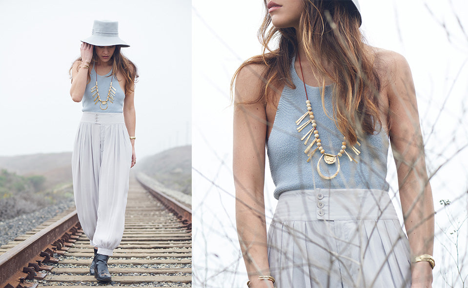 Woman walking down train tracks wearing El Sur Grande Necklace