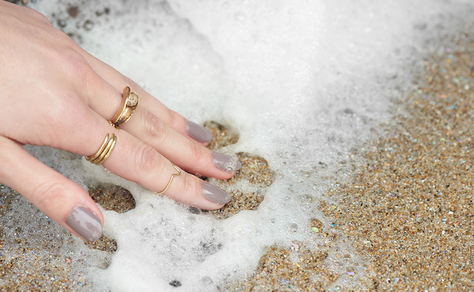 Well manicured hand touching seafoam on the beach, wearing Arma rings.