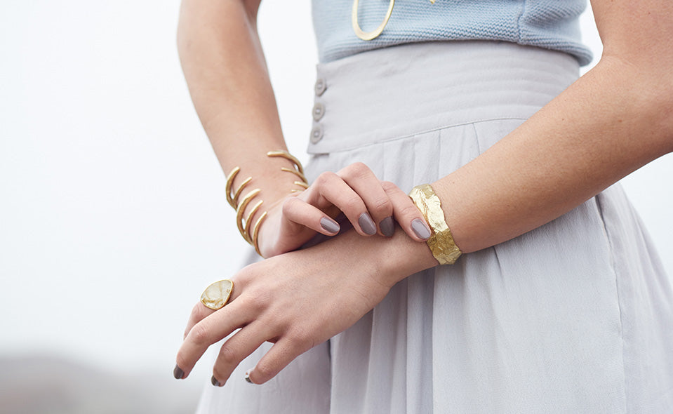 A woman's midsection, one hand touching her wrist, wearing a Coastal Cuff and various rings.