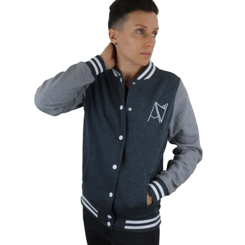 Model wearing two-tone varsity style jacket with Androgynous Fox badge logo stitched on left-side breast. Navy body with grey sleeve, snap front, pockets and blue and white stripe elastic detail.