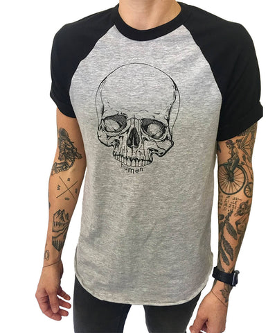 Model wearing Androgynous Fox short sleeve baseball tee with black sleeves and grey body. Skull is printed in black ink.