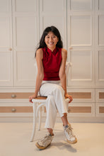 Load image into Gallery viewer, Model sitting down wearing a red slit top with chinese buttons paired with white pants and white sneakers