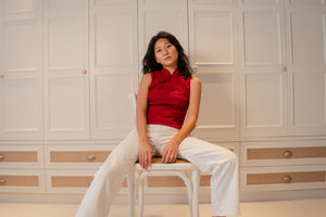 Model sitting down wearing a red slit top with chinese buttons paired with white pants and white sneakers