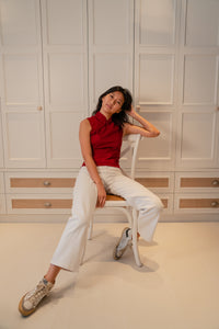 Model sitting down wearing a red slit top with chinese buttons paired with white pants and white sneakers brushing her hair